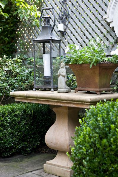 lantern, small stone statue, and a planter on top of a stone table in a backyard designed by kelley proxmire