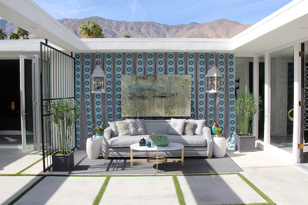 backyard patio with a stylish sofa, coffee table, side tables, a wall-mounted painting, and hanging lanterns, designed by lori dennis