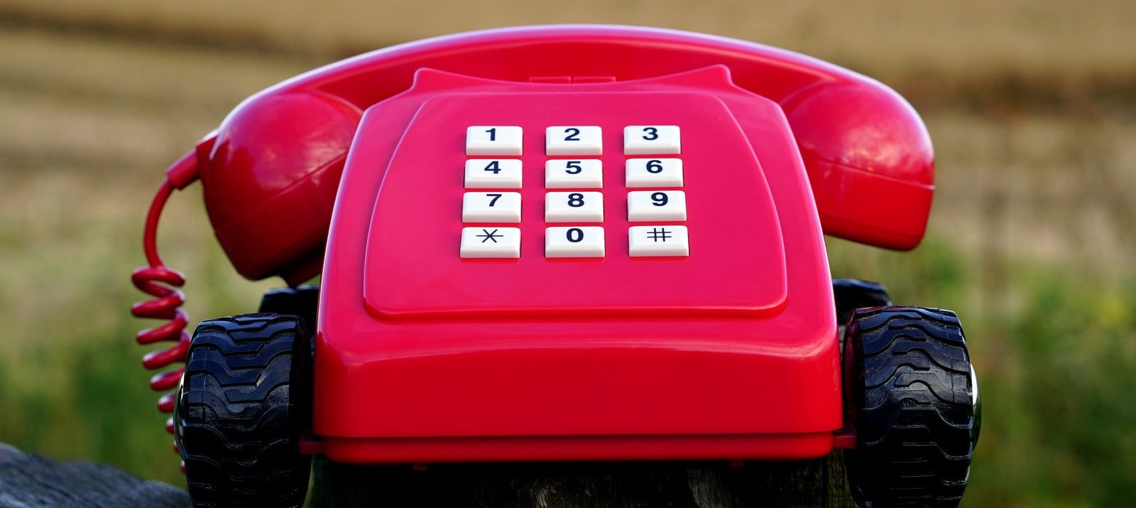 how to switch utilities and services when moving: red vintage phone on wheels