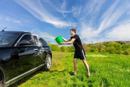 car garage spring cleaning checklist: guy washing his car in the grass
