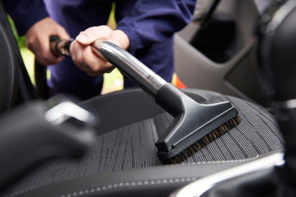 A person vacuuming his car seat.