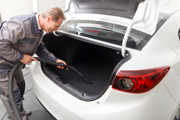 A man vacuums the trunk of his car.