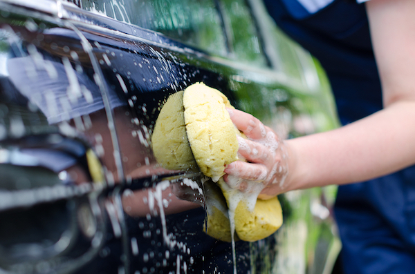 A woman wipes the outside of her car with a sponge.