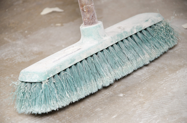 A dusty broom for sweeping the garage.
