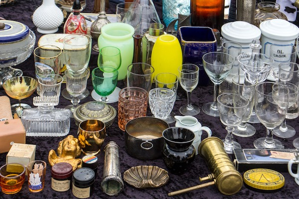 A table full of cups, bowls, and other miscellanea at a flea market.