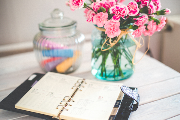 An open planner and flowers are on a vintage desk