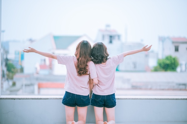 Two girls are celebrating with their hands in the air