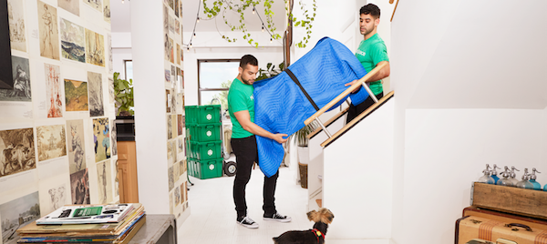 MakeSpace movers lifting a couch on the stairs