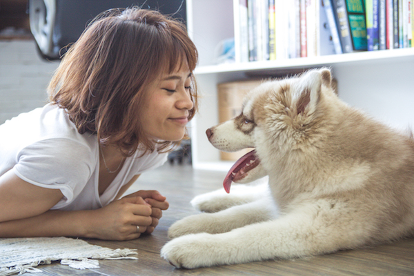 a woman smiles at her really cute dog
