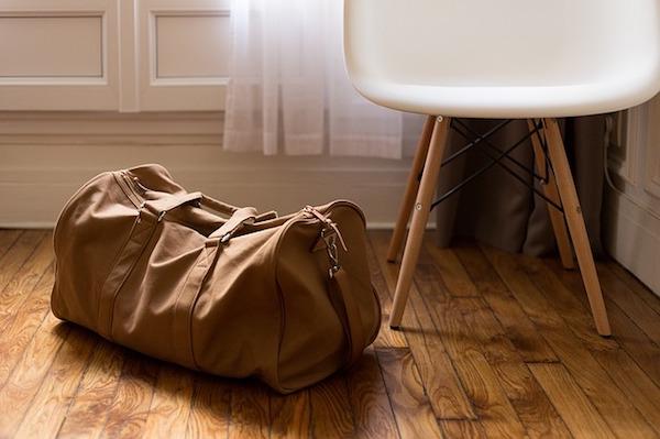 An overnight bag next to a chair