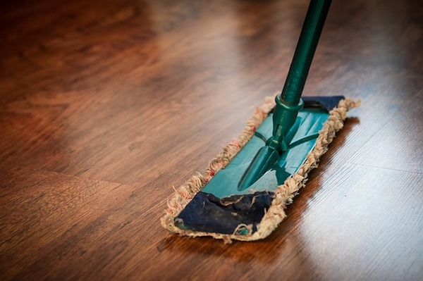 a green duster sweeps a hardwood floor