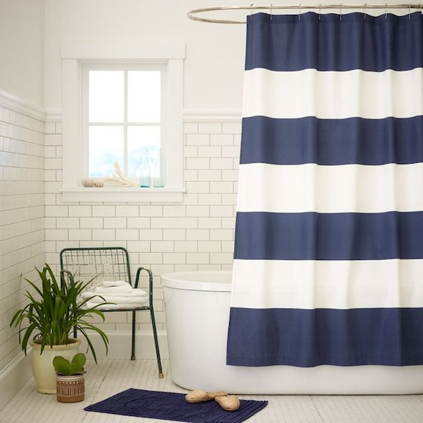 a white bathroom with a blue striped shower curtain
