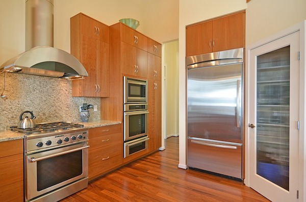 a kitchen with hardwood floors and steel appliances