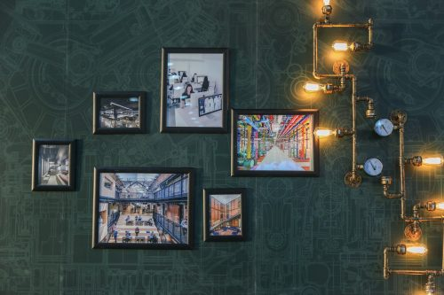 picture frames on a patterned wall being lit by lightbulbs