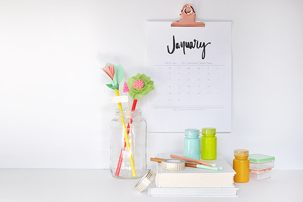 a hand-lettered calendar hanging above a desk with flowers on it