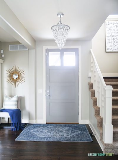 the entryway to a home with a hanging chandelier