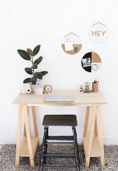 DIY cork boards hang above a desk with plants