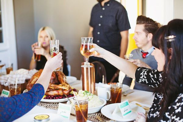 Friends gather for a Friendsgiving celebration and toast at the table