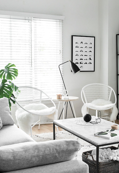 a peaceful white living room with two chairs and a sofa