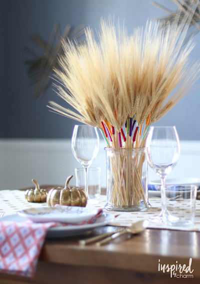 A stalk of wheat is wrapped with colorful strings on top of a Thanksgiving table