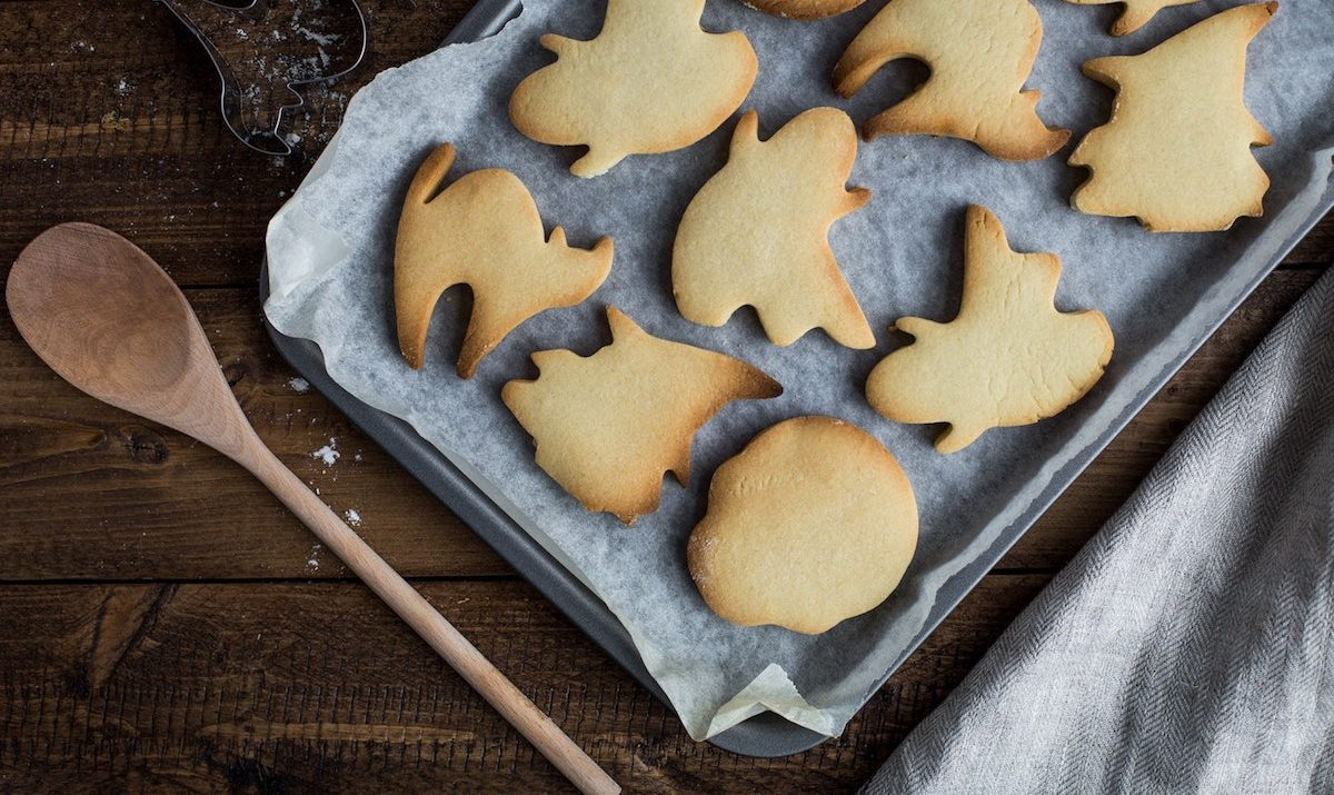 tray of holiday cookies next to a wooden spoon on a wooden table