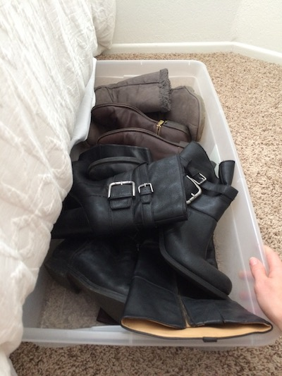 assorted boots stored in a clear storage bin without the lid
