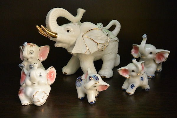 Porcelain elephants are lined up on a dark surface