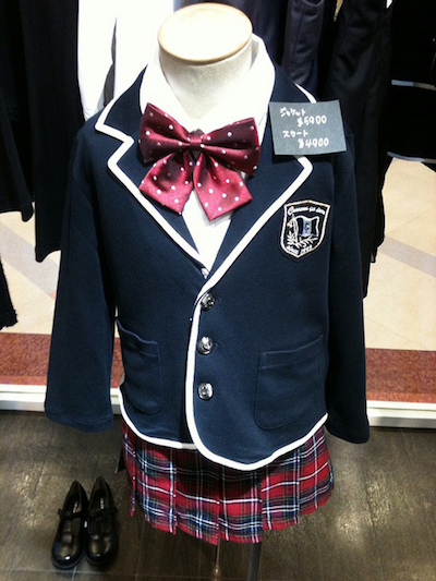 A child's school uniform complete with a satin bow and shoes