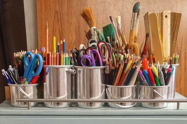 Colorful art supplies are grouped together in six tin canisters
