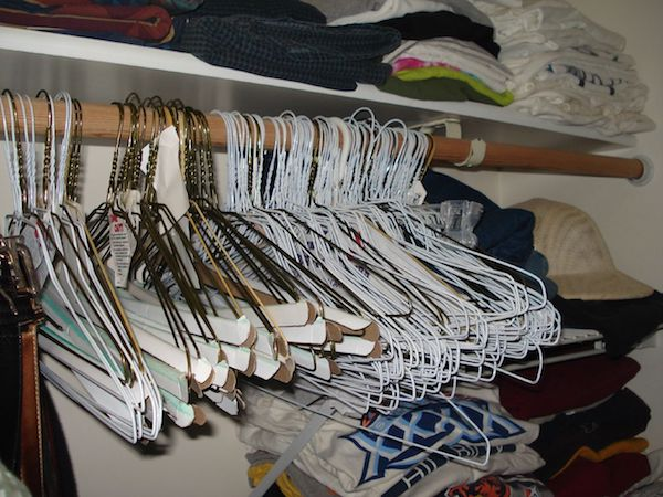 Old wire hangers are crammed together in a dimly lit closet