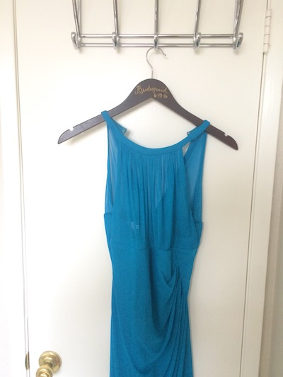 a formal blue bridesmaid dress hangs from the door, ready to be donated