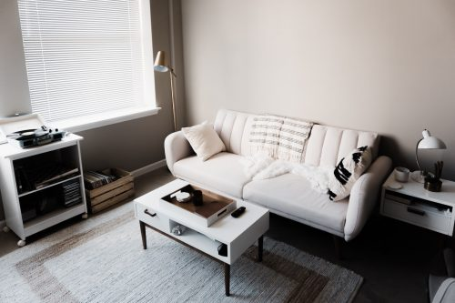 a clean apartment with white walls and a white sofa, end table, coffee table, and rolling shelving unit