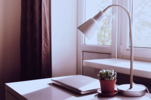 a macbook on a home office desk next to a window that's letting in a lot of natural light