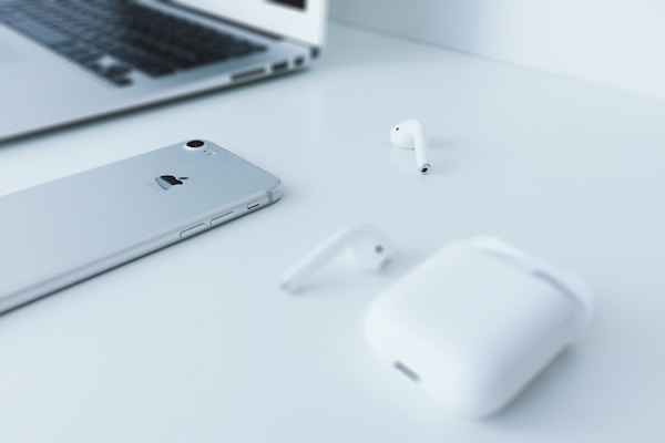 airpods are next to an iphone and a macbook air on a white home office desk