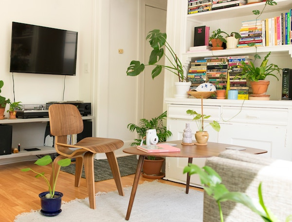 a wooden chair and small desk are a makeshift home office inside a living room