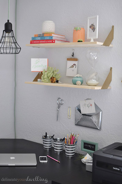 2 floating shelves are storing various household items above an organized desk and office supplies