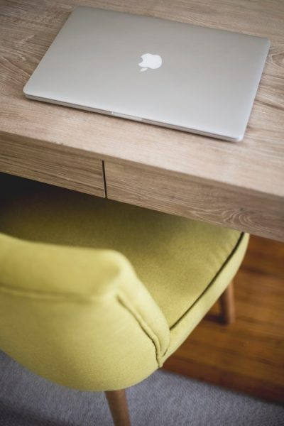a comfy chair is pushed in underneath a wooden desk with a laptop