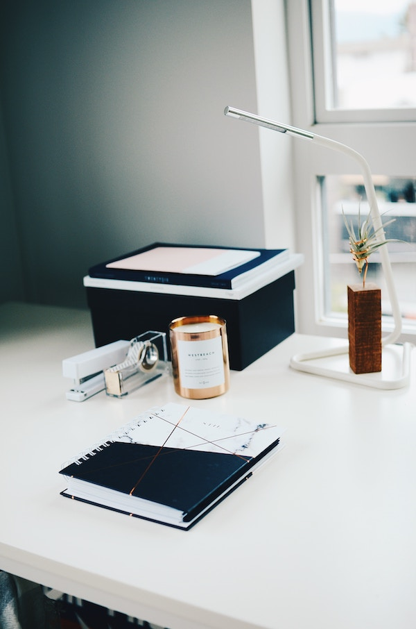 a desk with a printer and small reading lamp