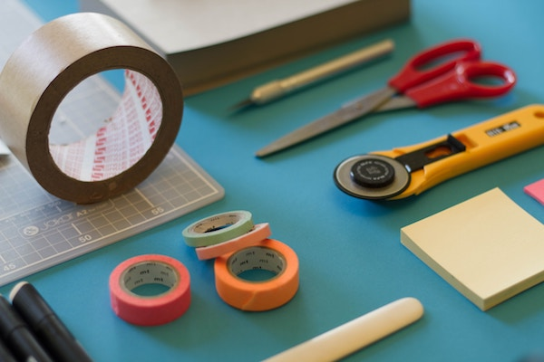 a table with office supplies like scissors, duct tape, and sticky notes