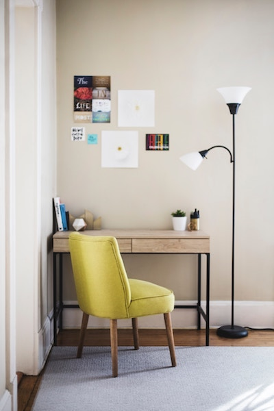 a clean and tidy desk sits next to a tall lamp and chair in a home