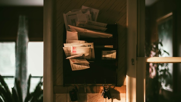 a pile of papers and mail cluttered together in a wall mail organizer