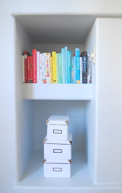 books are lined up in a small nook, under which is a stack of three storage boxes
