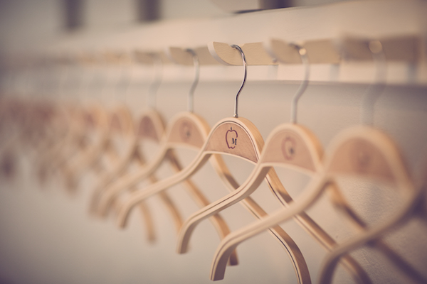 wooden hangers hanging on a wall-mounted board with hooks