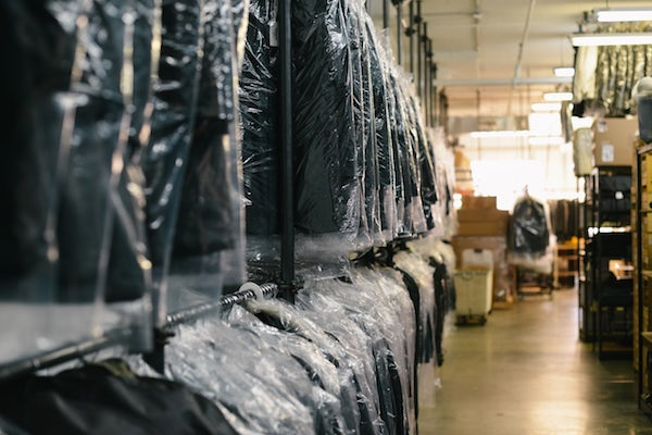 clothes in plastic dry cleaning bags are hanging on racks at the dry cleaners
