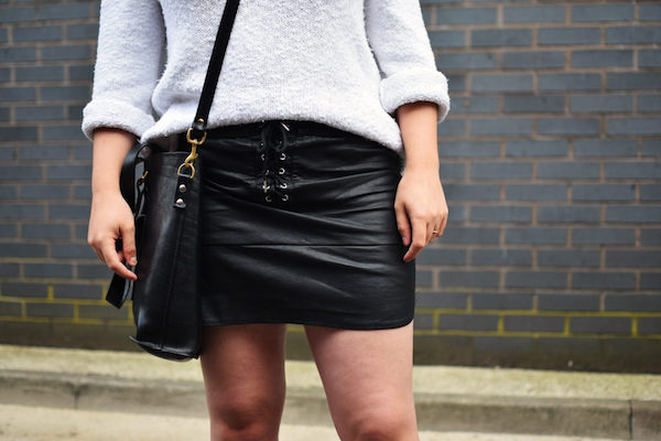 a girl wearing a black leather tie front mini skirt and a black bag over her left shoulder