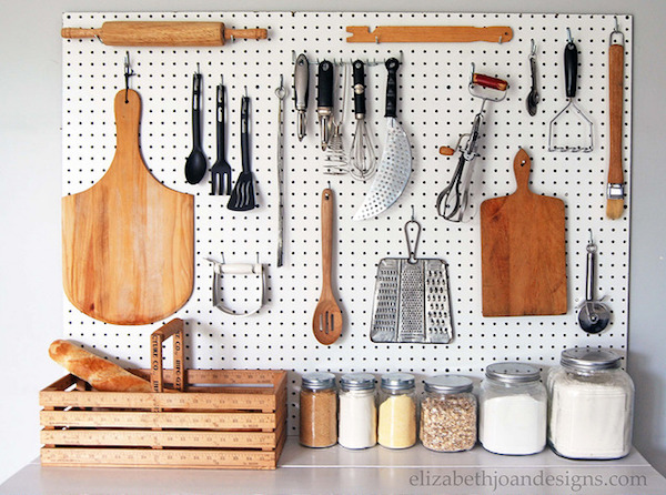 a pegboard hangs in the kitchen with cooking supplies like a cutting board and knives