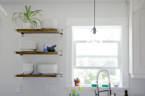 floating shelves hold plates and a plant near a window in a white kitchen