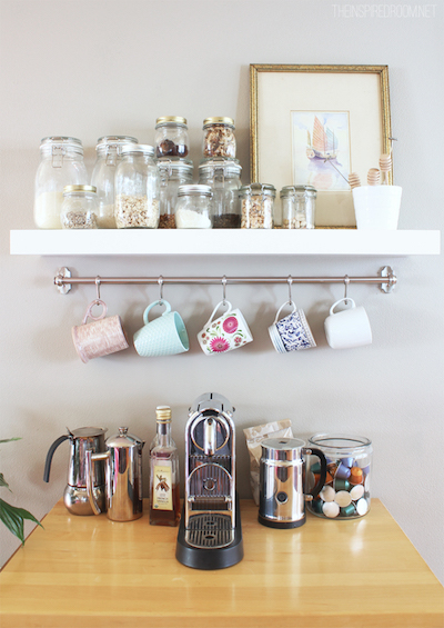 a small coffee station with a shelf and hanging rod that holds mugs