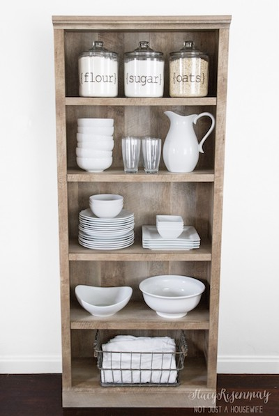 a large brown bookcase has been converted into a storage space for dishes