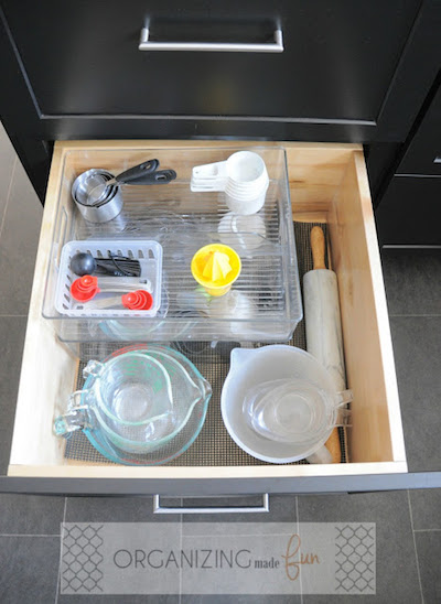 an organized kitchen drawer with items separated with clear containers and organizers